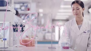 Woman in lab coat stands next to lab equipment